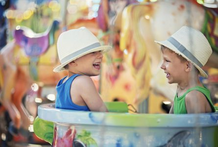 Two little brothers sitting in the same cup on carousel. The boys are aged 5 and wearing fedoras. Boys are having fun and laughing.